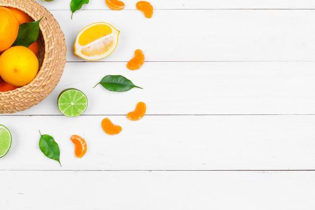 白い木製の背景、上面に柑橘系の果物のボウル