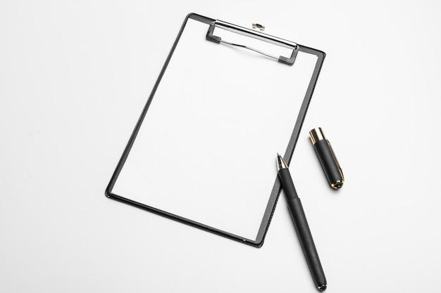 Доска сзажимом для бумаги с белым листом и изолированная ручка. вид сверху