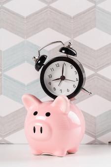 時間を節約するための目覚まし時計と貯金箱のコンセプト