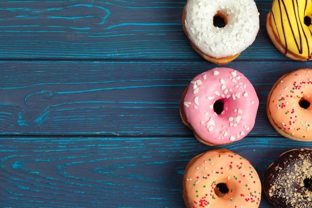 暗い青色の木製の背景にカラフルな新鮮なドーナツ