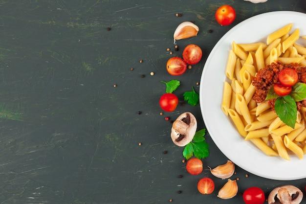 肉、トマトソース、野菜、テーブルの背景のパスタ