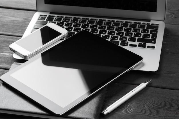 デジタルタブレットとスマートフォンで開いているラップトップをクローズアップ