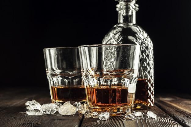 Стакан виски и бутылка на старый деревянный стол