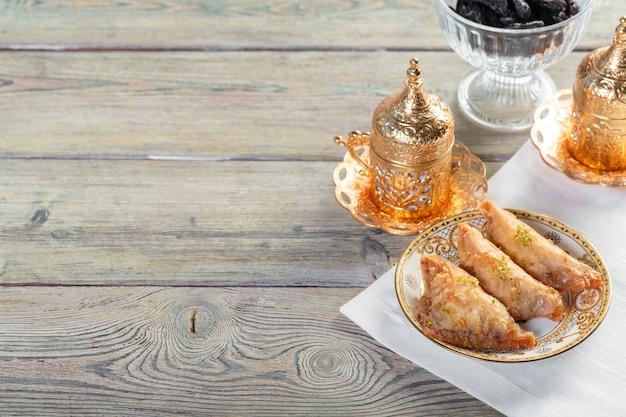 木製のテーブルにユーカリの枝とカシューナッツ、クルミ、カルダモンと伝統的なアラビア語のデザートバクラヴァ
