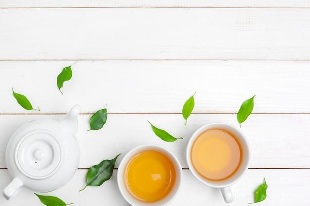 ティーポットと白い木製の背景にお茶のカップ