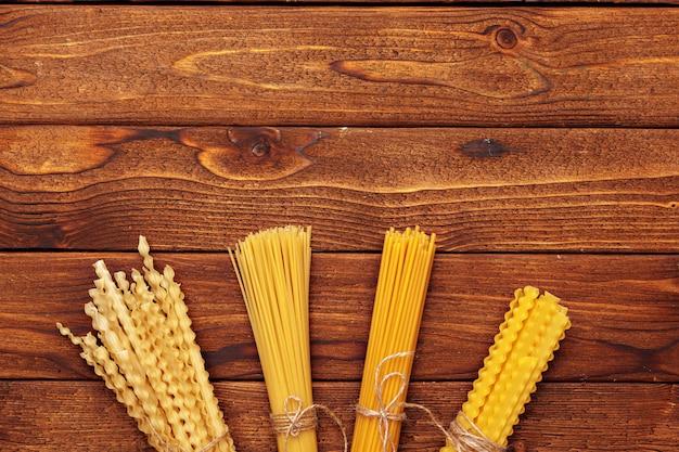 木製の背景に乾燥パスタ