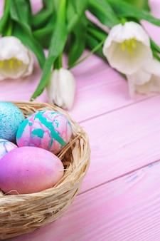 カラフルな卵とピンクの木の上にチューリップのイースター。コピースペースのトップビュー