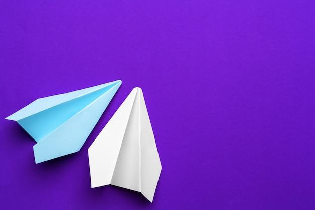 紫色の背景にホワイトペーパー飛行機