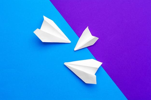 カラーブロックブルーとパープルのホワイトペーパー飛行機