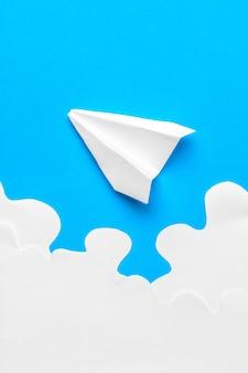 Летающий бумажный самолетик в облаках. концепция полета, путешествия