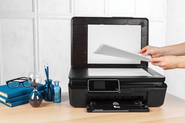 Неузнаваемая молодая деловая женщина делает копии на фотокопировальной машине в офисе