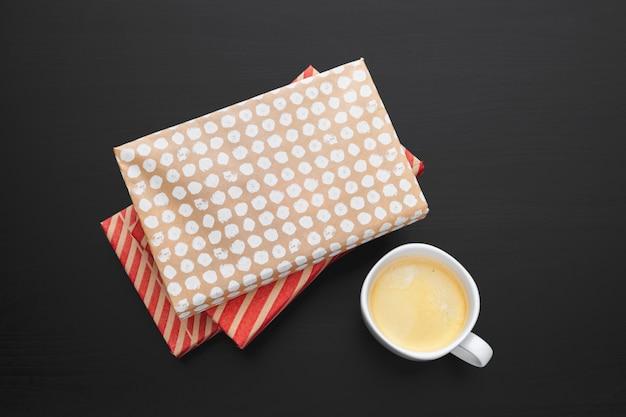 一杯のコーヒーと木製デッキ卓上の本