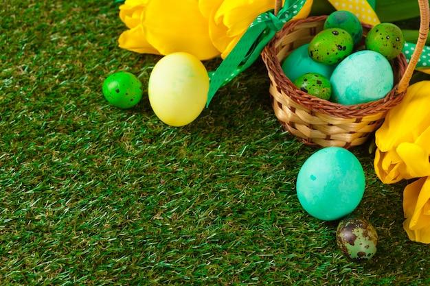 緑の草の上に花とイースターエッグ