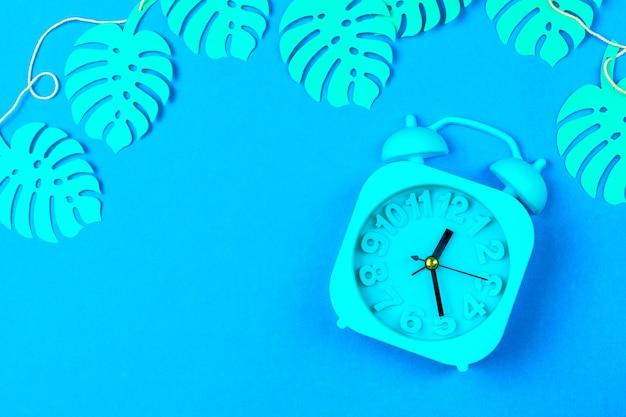目覚まし時計と熱帯の葉