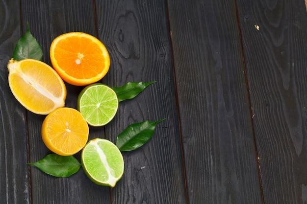 黒い木製の背景に柑橘系の果物のスライス