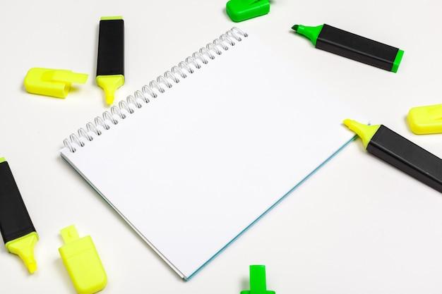 蛍光ペンと空白のメモ帳用紙は机の上に横たわっていた