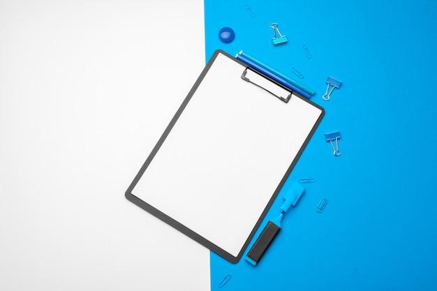 活気のあるダブルトーンの青と白の背景にモックアップのクリップボード