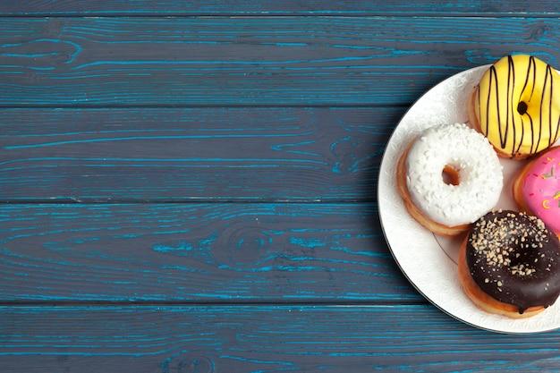 暗い青い木製の表面の背景にカラフルな新鮮なドーナツ
