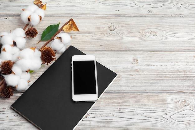 テーブルの上の携帯電話と枝の綿の花。上面図。