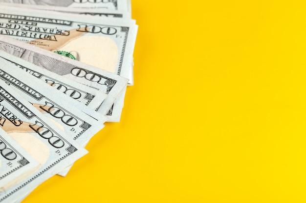 黄色の背景に米ドルの現金。