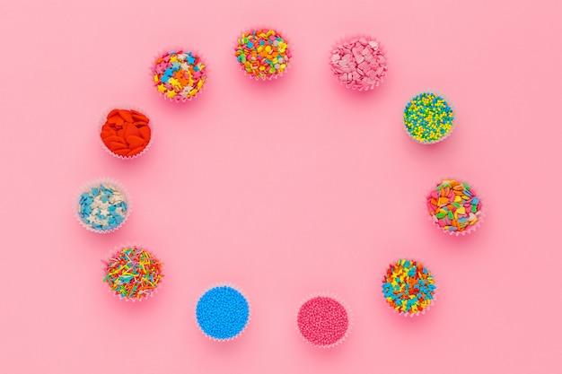Сахарная посыпка, украшение для торта и мороженого и печенье на розовом фоне