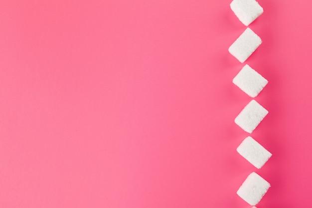 明るいピンクの背景に砂糖のキューブ