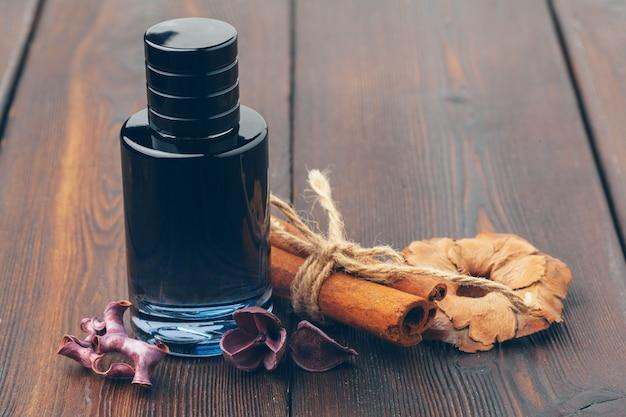 Черная бутылка духов на деревянный стол