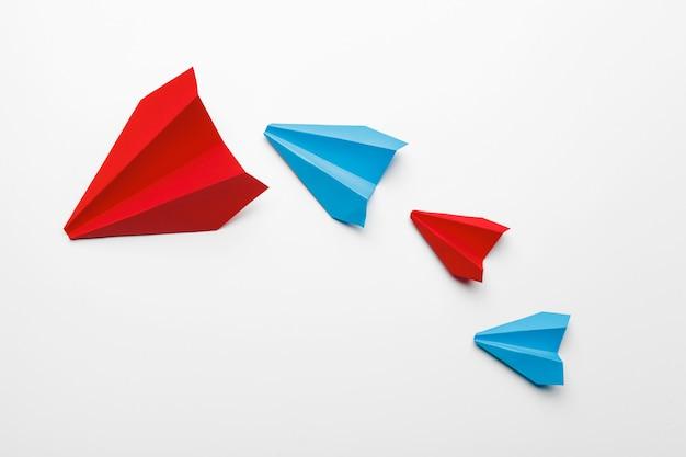 Красные и синие бумажные самолетики на белом фоне
