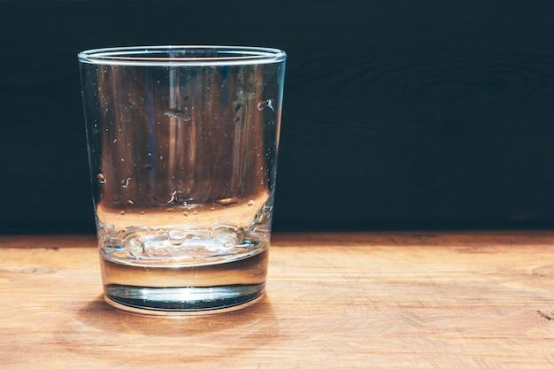 暗い背景上の水のガラスをクローズアップ