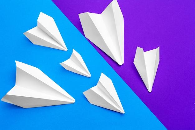 Белый бумажный самолетик на голубой и фиолетовой бумаге