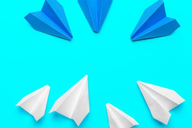 青色の背景に紙飛行機のグループ。新しいアイデアの創造性と革新的なソリューションの概念のためのビジネス