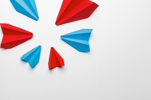 白地に赤と青の紙飛行機。リーダーシップとビジネス競争の概念