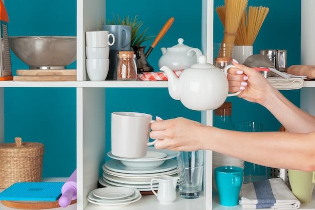 台所の棚から台所用品を取る女性の手