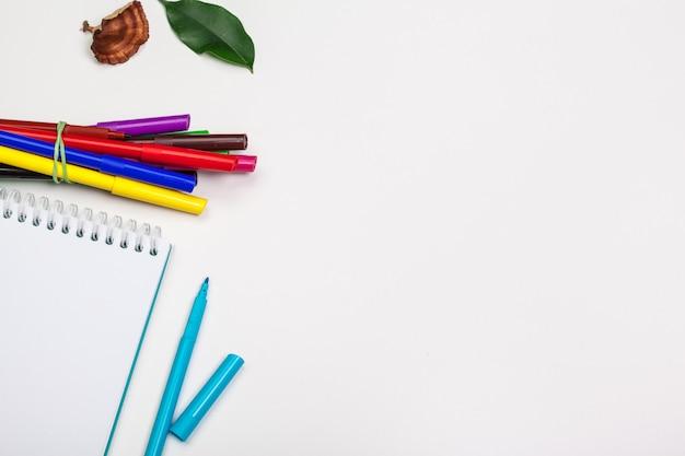 さまざまな色のフェルトチップマーカーと空白のスケッチブックのセット