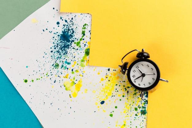ペイント振りかけると創造的なカラフルな背景にビンテージの目覚まし時計