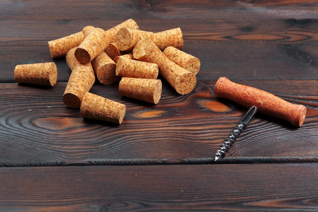 木製のテーブルにコルク栓抜きとワインのコルク