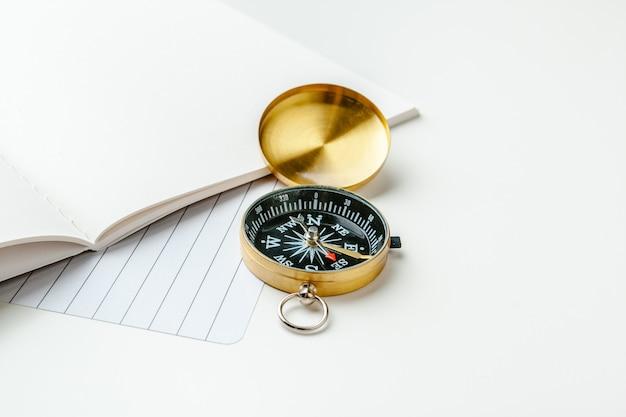 航海ノートと白いテーブルの上の黄金の羅針盤の黒いメモ帳
