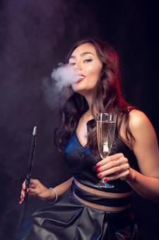 素敵な女性シーシャ喫煙とバーでカクテルを飲む