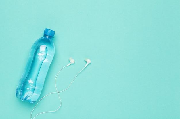 水のボトル、イヤホン付き携帯電話でのフィットネス
