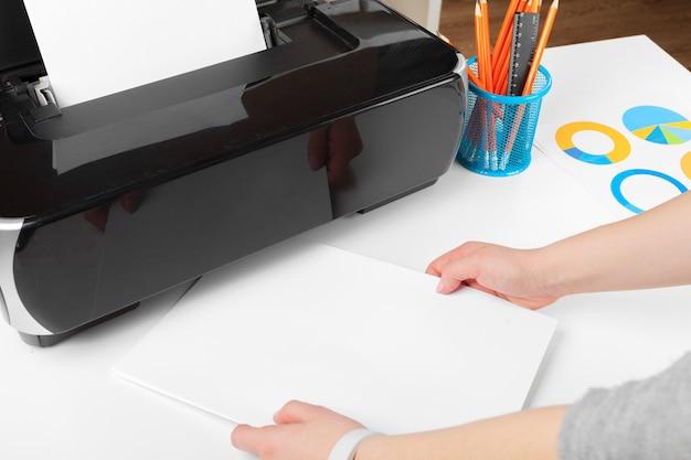 プリンターを使用してドキュメントをスキャンおよび印刷する女性
