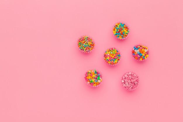Сахар брызгает на розовом фоне