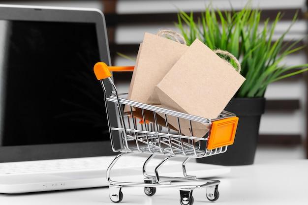 ミニショッピングカートと机の上のノートパソコン