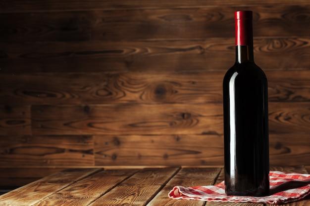 木製の背景の上のワインのボトル