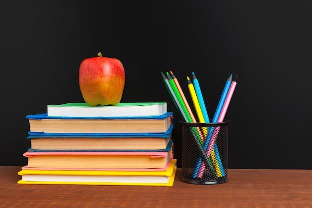 本と木製の机の上のリンゴと黒板