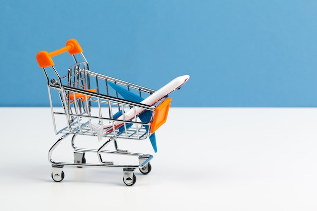 白いテーブルの上のおもちゃの航空機でショッピングトロリーをクローズアップ