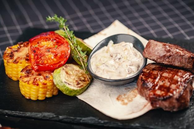 灰色のスレート背景に野菜と牛肉のグリルステーキ