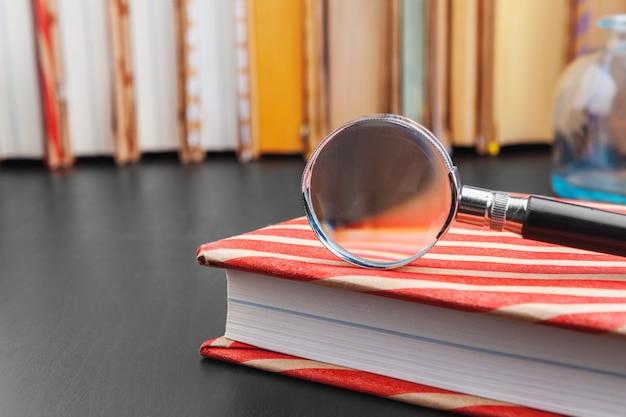 Книга и увеличительное стекло на деревянном