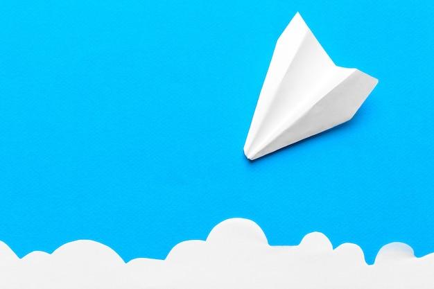 青色の背景に雲の中で飛ぶ紙飛行機。飛行、旅行、乗り換えの概念