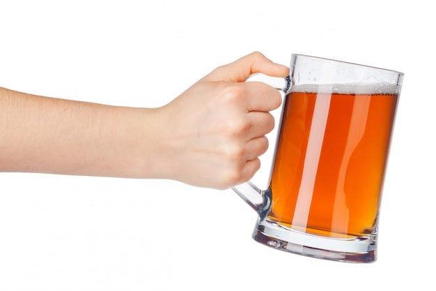 白で隔離される完全なビールのグラスを持つ手