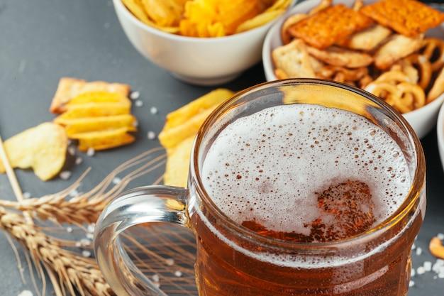 石のテーブルでラガービールとスナック。クラッカー、チップの側面図